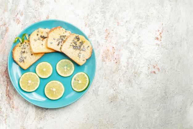 Сверху крупным планом хлеб и нарезанные лимоном цитрусовые и белый хлеб на тарелке с левой стороны стола