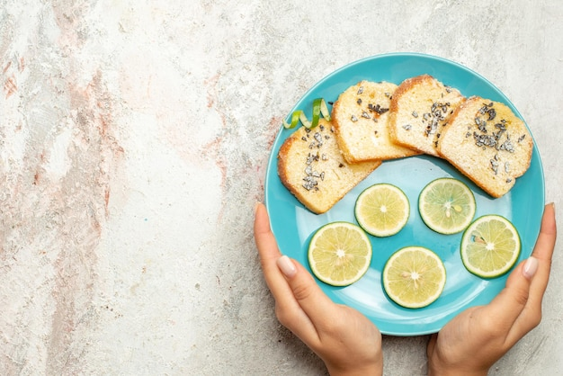 Top close-up view bread and lemon blue plate of bread and sliced lemon in hand on the white table
