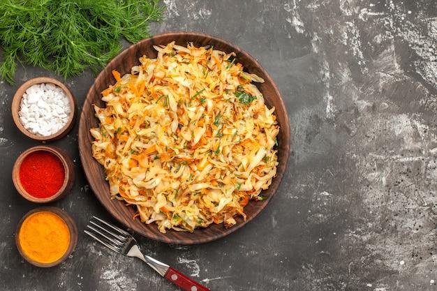 Top vista ravvicinata cavolo erbe piatto di cavolo forchetta ciotole di spezie