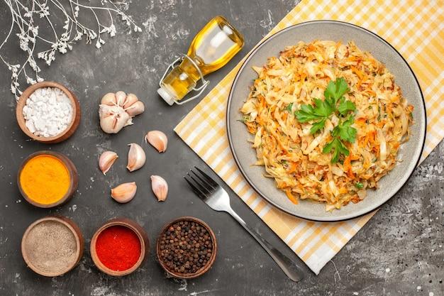 Top vista ravvicinata piatto di cavolo di cavolo cappuccio sulla tovaglia aglio bottiglia di olio spezie forcella