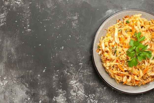 テーブルの上にニンジンハーブと食欲をそそるキャベツの上部のクローズアップビューキャベツプレート