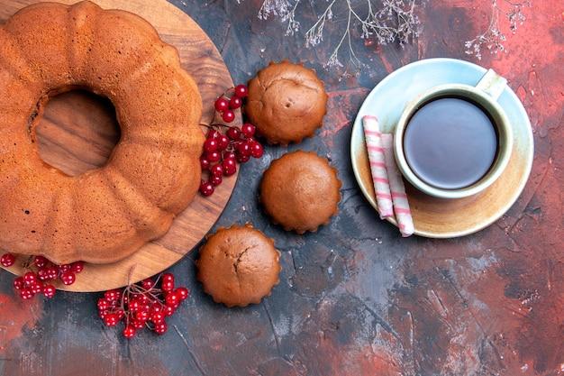 上のクローズアップビューケーキボードカップケーキの木の枝に赤スグリとお茶のケーキのカップ