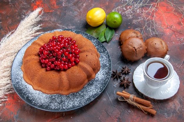 トップクローズアップビューケーキベリーと食欲をそそるケーキお茶の柑橘系の果物のカップ