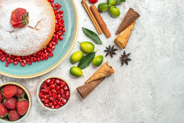 Top close-up view a cake an appetizing cake bowls of berries limes cinnamon sticks citrus fruits