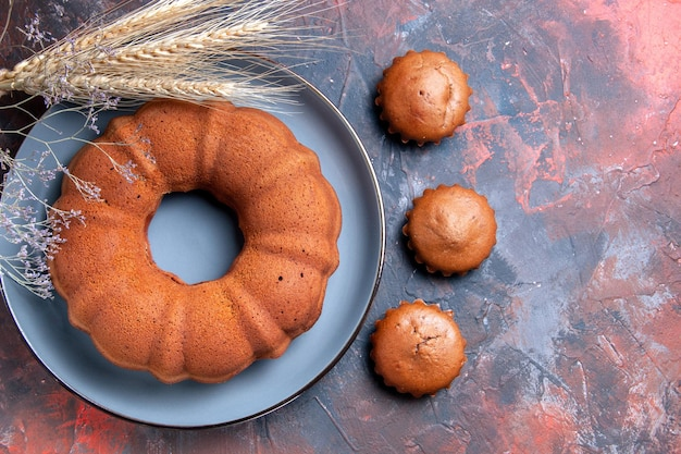 Vista ravvicinata dall'alto una torta la torta appetitosa e tre cupcakes spighe di grano rami di albero