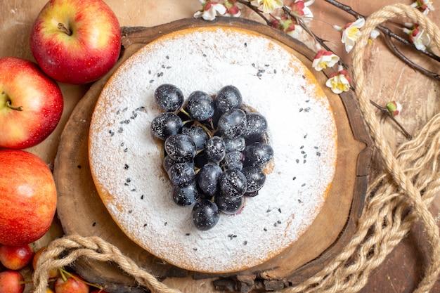Top vista ravvicinata una torta una torta appetitosa con l'uva sulla corda di bordo mele bacche