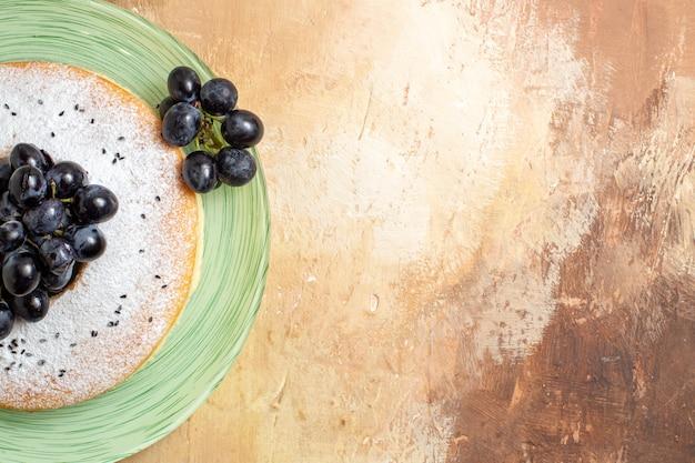 Vista ravvicinata dall'alto una torta una torta appetitosa con l'uva sul piatto verde