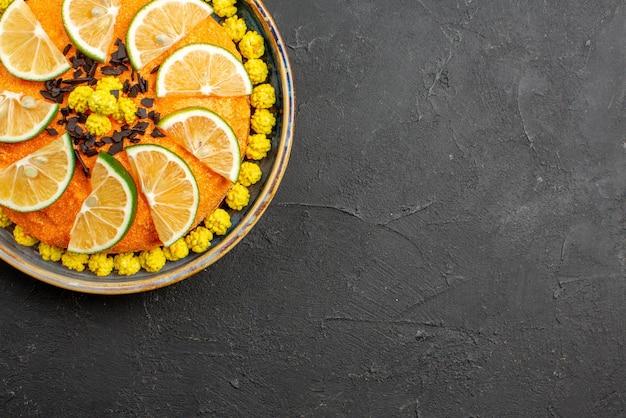 Сверху крупным планом торт аппетитный торт с нарезанными цитрусовыми фруктами на левой стороне темного стола