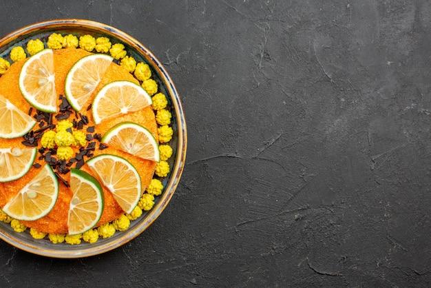 어두운 탁자의 왼쪽에 감귤류 과일 조각이 있는 식욕을 돋우는 케이크