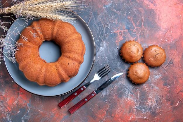 Vista ravvicinata dall'alto una torta i cupcakes appetitosi torta forchetta coltello spighe di grano e rami