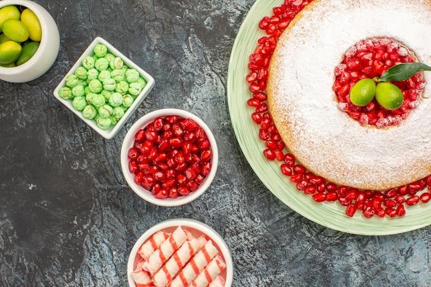 Сверху крупным планом миски для торта с конфетами, аппетитный торт на тарелке