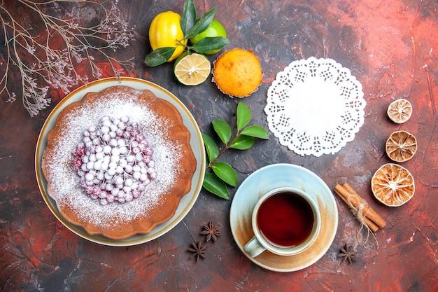 Vista ravvicinata dall'alto torta una torta con frutti di bosco agrumi cupcake pizzo centrino una tazza di tè