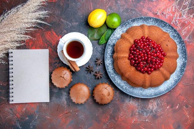 Vista ravvicinata dall'alto torta torta con frutti di bosco agrumi cupcakes una tazza di tè quaderno anice stellato