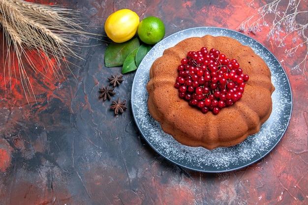 Vista ravvicinata dall'alto torta torta con bacche limoni foglie di lime anice stellato spighe di grano