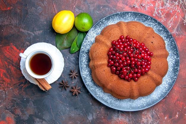 딸기 라임 레몬을 곁들인 클로즈업 보기 케이크 케이크 한 컵의 차 스타 아니스 잎