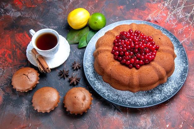 Vista ravvicinata dall'alto torta torta con bacche lime limone foglie cupcakes una tazza di tè anice stellato
