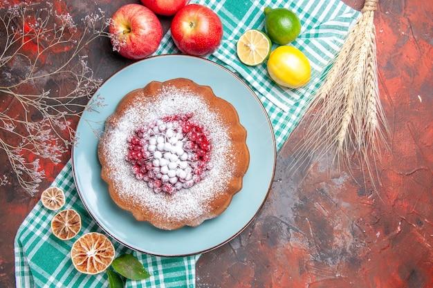Vista ravvicinata dall'alto una torta una torta con frutti di bosco zucchero a velo agrumi mele spighe di grano