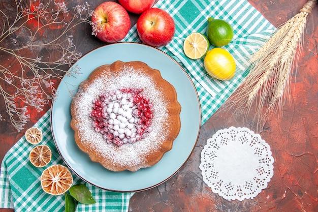 Vista ravvicinata dall'alto una torta una torta con frutti di bosco e zucchero centrino di pizzo agrumi mele spighe di grano