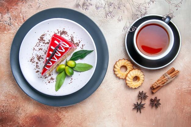 Top vista ravvicinata una torta torta con salse al cioccolato agrumi una tazza di tè biscotti alla cannella