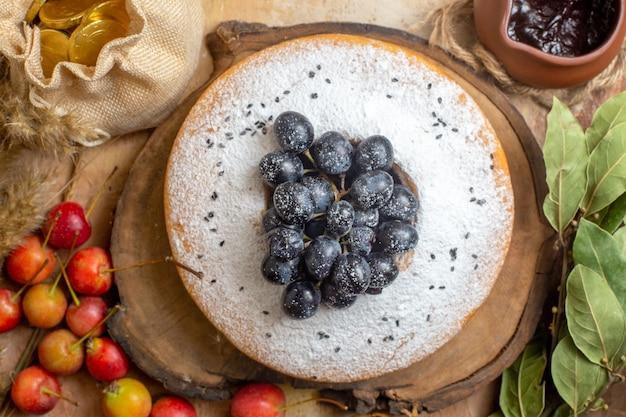Vista ravvicinata dall'alto una torta una torta con l'uva sul bordo bacche salsa al cioccolato foglie