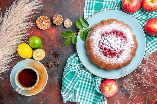 Vista ravvicinata dall'alto una torta una torta con mele di zucchero a velo una tazza di tè agli agrumi