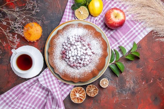 Vista ravvicinata dall'alto una torta una tazza di tè una torta mela limoni con foglie sulla tovaglia cupcake