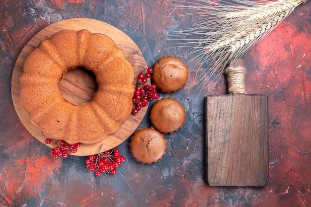 Vista ravvicinata dall'alto tagliere dei cupcakes della torta accanto alla torta dei cupcakes con ribes rosso