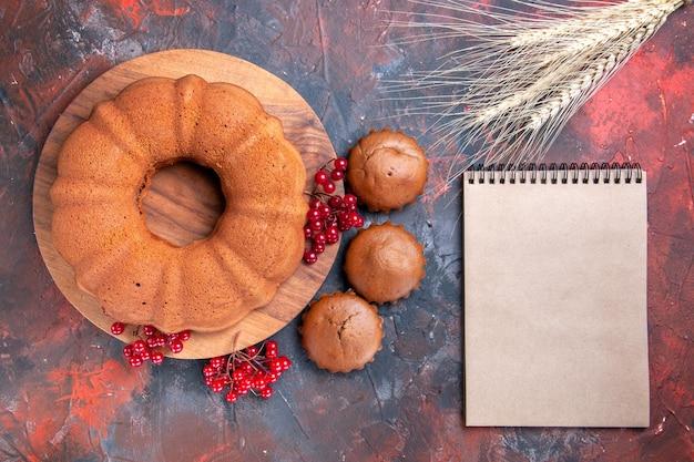 Vista ravvicinata dall'alto torta cupcakes tre cupcakes una torta con ribes rosso spighe di grano quaderno