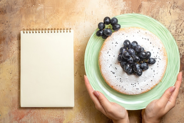 Top close-up view a cake green plate of an appetizing cake with grapes in hands notebook