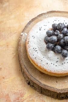 Top vista ravvicinata torta il bordo della cucina con una torta con uva nera e zucchero a velo
