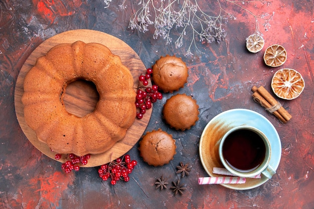 Vista ravvicinata dall'alto torta limone cannella anice stellato una tazza di torta da tè con cupcakes al ribes rosso