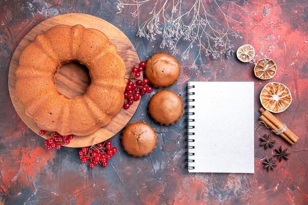 Top close-up view cake lemon cinnamon sticks star anise white notebook cake and tasty cupcakes
