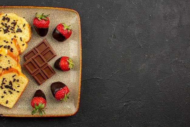 테이블 왼쪽에 있는 정사각형 회색 접시에 초콜릿과 초콜릿으로 덮인 딸기가 있는 접시 케이크 위에 클로즈업 보기 케이크