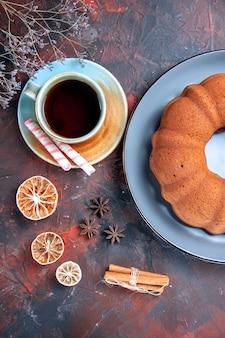 Vista ravvicinata dall'alto un piatto di torta una tazza di tè, limone, anice stellato, cannella, dolci