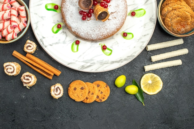 Top vista ravvicinata un piatto di torta di torta con cialde agrumi biscotti bastoncini di cannella dolci