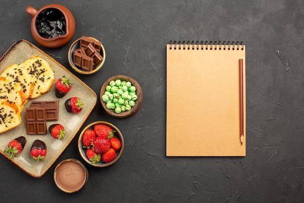 Vista ravvicinata dall'alto torta e fragole piatto di torta e ciotole di fragole al cioccolato caramelle verdi e crema al cioccolato accanto al quaderno con la matita