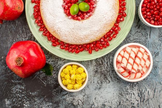 Vista ravvicinata dall'alto torta dolci una torta due melograni ciotole di caramelle colorate