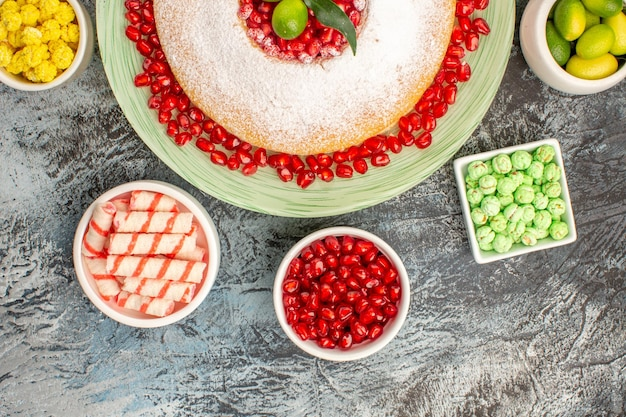 Vista ravvicinata dall'alto torta dolci una torta con semi di melograno ciotole di agrumi caramelle verdi
