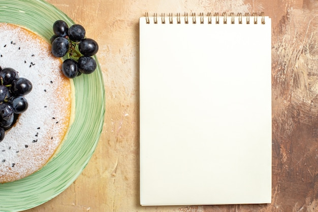 Top close-up view a cake white notebook an appetizing cake with grapes