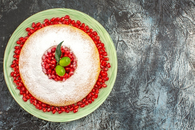 Top close-up view cake with berries an appetizing cake with seeds of pomegranate and citrus fruits