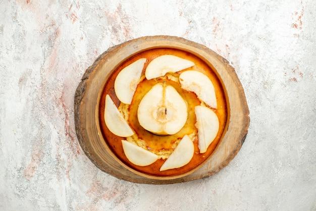 ライトテーブルの木の板に梨のおいしいケーキと梨のトップクローズアップビューケーキ