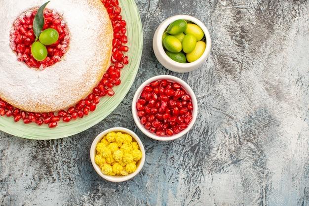 Torta con vista ravvicinata dall'alto con melograno un piatto di torta con melograni e ciotole di frutti di bosco