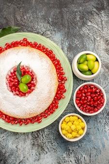 Vista ravvicinata dall'alto torta con melograno tre ciotole di frutti di bosco un piatto di torta con melograno
