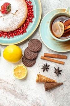 Top close-up view cake with strawberries cinnamon a cup of tea with lemon the cake cookies