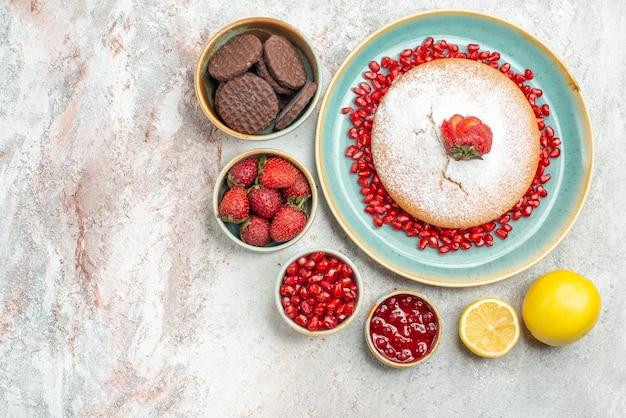 Torte vista ravvicinata dall'alto con melograno piatto di torta di fragole e semi di melograno biscotti al limone sul tavolo