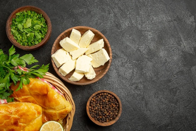 Top close-up view cheese herbs bowls of black pepper herbs and cheese and basket of an appetizing pies lemon herbs and checkered tablecloth on the table