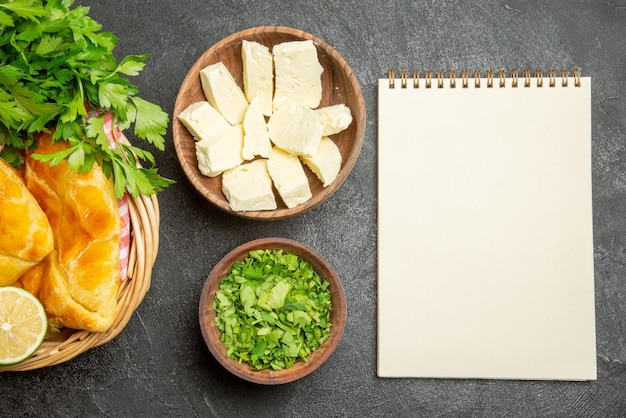 Top close-up view cheese herbs white notebook next to the bowls of herbs and cheese and basket of an appetizing pies lemon herbs and checkered tablecloth