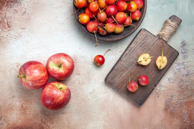 上部のクローズアップビューさくらんぼの木の枝さくらんぼのボウルとボード上の3つのリンゴ