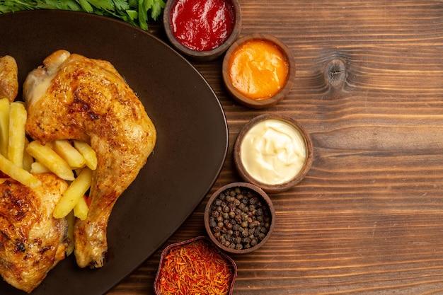 トップクローズアップビューチキンとスパイスの食欲をそそるチキンの脚フライドポテトとさまざまなソースとスパイスのボウル