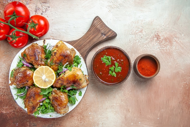 Top close-up view chicken the appetizing pieces of chicken with lemon herbs spices tomatoes sauce